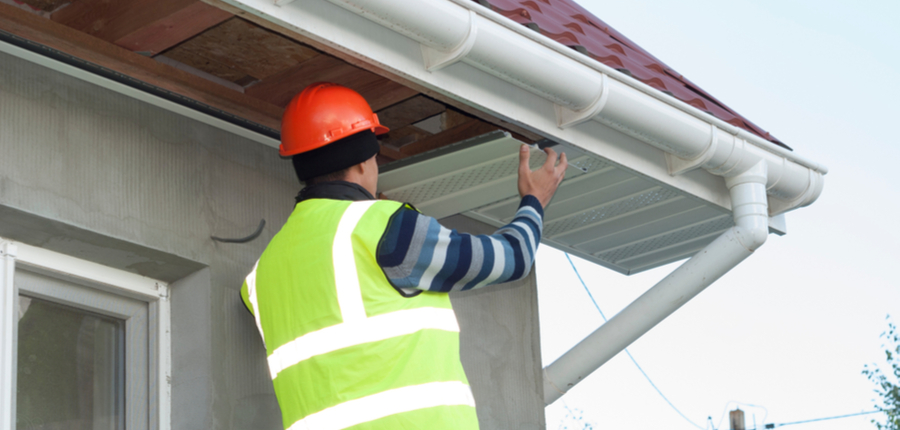 construction worker mounts a soffit on the roof