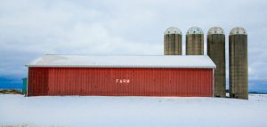 red pole barn with four silos