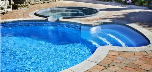 outdoor in ground swimming pool in backyard with hot tub