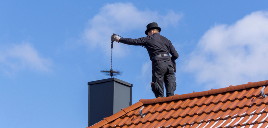 cleaning a chimney standing on the house roof