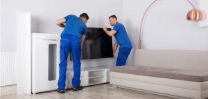 two young male movers placing a television
